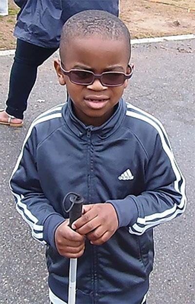Photo of young Christopher with his identification cane and sunglasses on