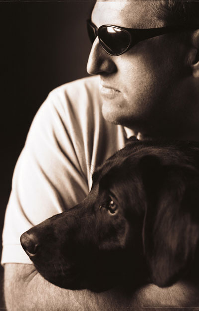 Photo of Cliff Hembree with his black Labrador retriever
