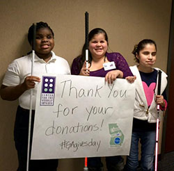 blind girls holding a thank you for your donation sign