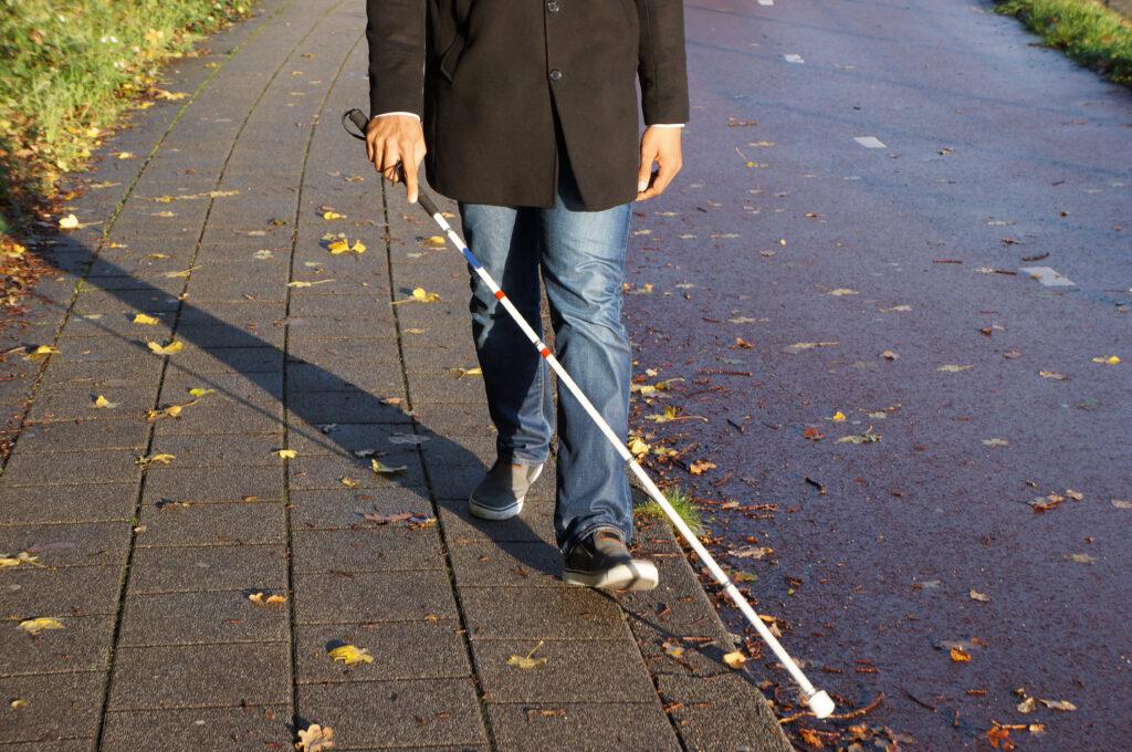 Person using white cane walking along sidewalk